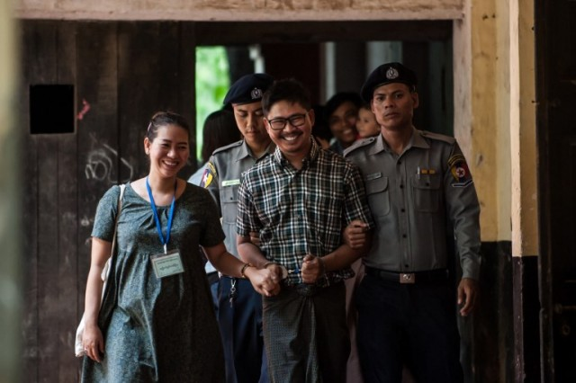 Detained Myanmar journalist Wa Lone (C) is escorted by police for his ongoing trial at a court in Yangon on May 29, 2018